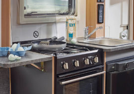 D4-3-kitchen-with-drop-down-kitchen-worktop-Thetford-combination-oven-grill-and-three-gas-burner-hob-and-Dometic